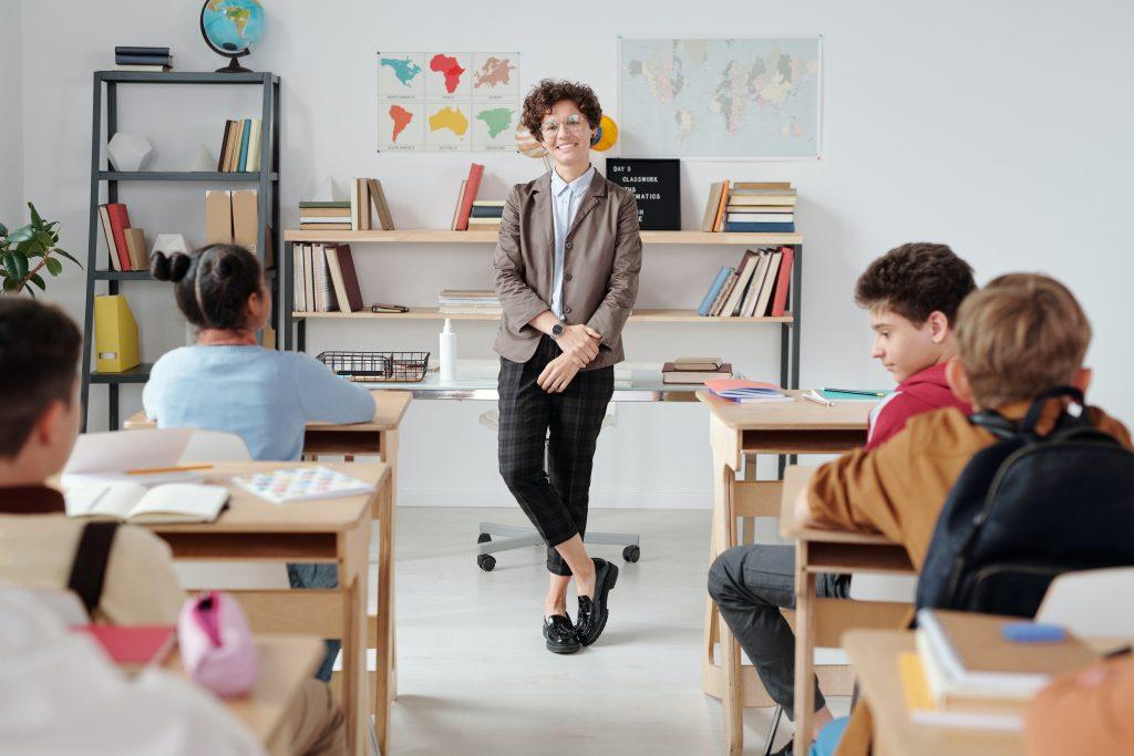 Professora ministrando aula para o Ensino Fundamental representando a atuação de quem estuda na faculdade de Letras.