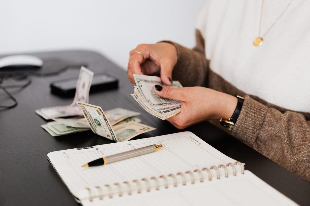 Pessoa contando dinheiro do salário.